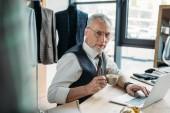 Fotografie schöne Reife Schneider arbeiten mit Laptop und Kaffeetrinken am Nähwerkstatt