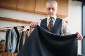 Fotografia sarto bello maturo con il panno grigio al laboratorio di cucito