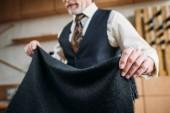 Fotografia ritagliata colpo di sarto maturo con il panno grigio al laboratorio di cucito