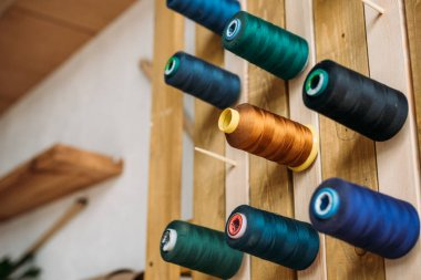 colored thread coils hanging on wooden wall at sewing workshop