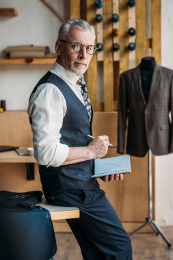 senior tailor holding notebook and pencil at sewing workshop and looking at camera