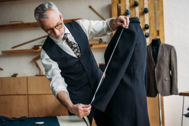 senior tailor measuring jacket sleeve with tape measure at sewing workshop