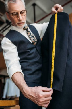 senior tailor measuring sleeve of jacket with tape measure at sewing workshop