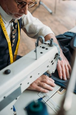 handsome professional tailor sewing cloth with sewing machine at sewing workshop