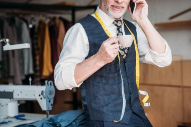 cropped image of tailor standing with cup of coffee and talking by smartphone at sewing workshop