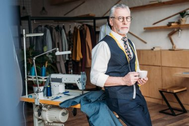 handsome tailor standing with cup of coffee at sewing workshop