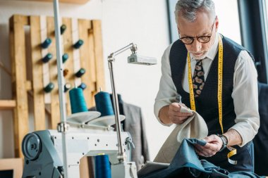 handsome tailor choosing between dark and light clothes at sewing workshop