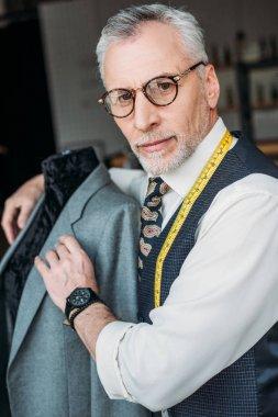 handsome tailor hugging mannequin with jacket at sewing workshop