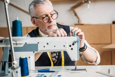 concentrated mature tailor working with modern sewing machine at workshop