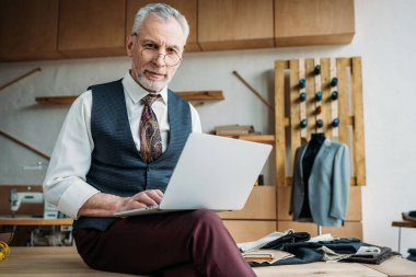 stylish mature tailor working with laptop while sitting on table at sewing workshop