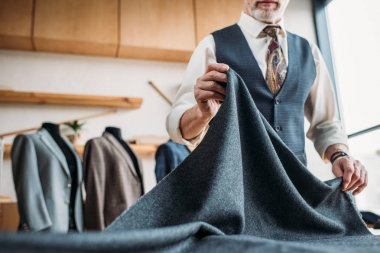 cropped shot of stylish mature tailor with grey cloth at sewing workshop