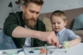Fotografie otec a roztomilý malý syn hrát s různými hračky dinosaurů dohromady doma