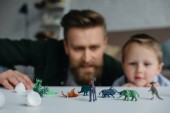 Photo selective focus of father and cute little son looking at arranged toy dinosaurs on tabletop together at home