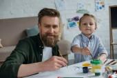 aranyos kis Atyáról, festékek és ecsetek látszó-on fényképezőgép együtt otthon és mosolyogva
