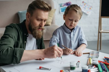 Father and cute little son with colorful pencils drawing pictures together at home stock vector