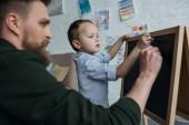 Fotografie Seitenansicht der kleine Junge und Vater mit Stücken der Kreidezeichnung Bild auf Tafel zu Hause