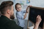 boční pohled na malý chlapec a otec s kousky křídy kreslení obrázku na tabuli doma