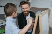 Fotografia ragazzino e padre sorridente con pezzi di gesso illustrazione immagine sulla lavagna a casa