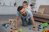 mosolygó apa és kisfia szórakozás együtt otthon