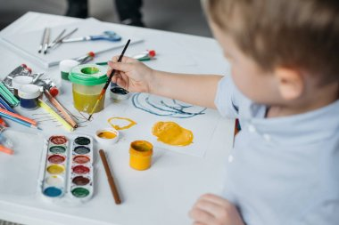 selective focus of little boy with brush and paintings drawing picture alone at home