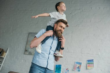 smiling father with little son sitting on shoulders having fun at home