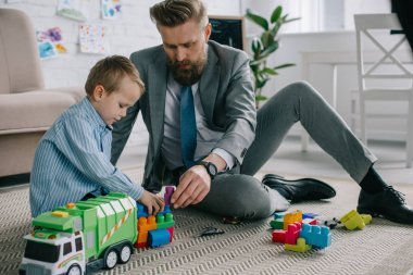 businessman in suit and little son playing with colorful blocks together on floor at home, work and life balance concept
