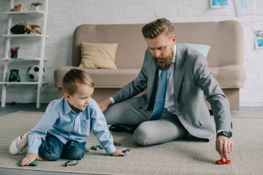 businessman in suit and little son playing with toy cars on floor at home, work and life balance concept