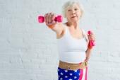 Aktive Seniorin turnt mit Hanteln und schaut weg