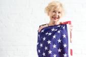 beautiful senior woman holding american flag and smiling at camera