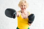 Glückliche Seniorin in Boxhandschuhen beim Training und lächelt in die Kamera