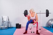 Fotografie smiling senior woman in sportswear sitting and training with dumbbells in gym