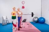 krásná starší sportovců stojící s překřížením rukou a usmívá se na kameru v tělocvičně