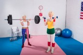 smiling senior sportswomen exercising with dumbbells and barbell in gym
