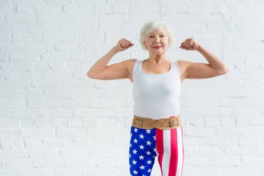 happy senior sportswoman showing muscles and smiling at camera