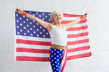Happy senior woman in sportswear holding american flag and smiling at camera stock vector