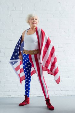 proud senior sportswoman posing with american flag and smiling at camera