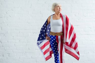 serious senior sportswoman holding us flag and looking away