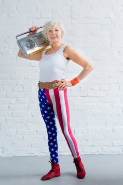 happy senior woman in sportswear holding tape recorder and smiling at camera