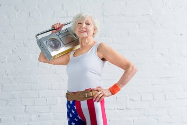 senior woman in patriotic sportswear holding tape recorder and smiling at camera