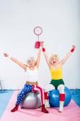 Fotografie nadšený senior sportovců sedí na fitness míče a usmívá se na kameru