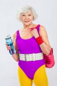 Fotografie beautiful smiling senior sportswoman holding bottle of water and boxing gloves
