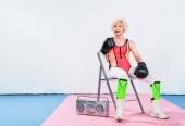 Fotografie Sportive starší žena v Boxerské rukavice poslech hudby a hledat dál