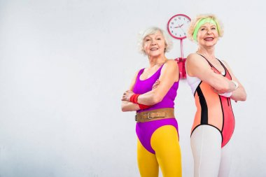 low angle view of happy senior sportswomen standing with crossed arms and smiling at camera