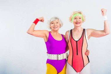 happy senior sportswomen showing muscles and smiling at camera isolated on grey