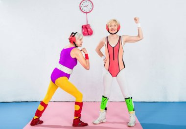 full length view of beautiful senior female wrestlers in sportswear and head protection