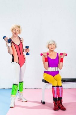 Sporty senior women in sportswear exercising with dumbbells and smiling at camera in gym stock vector