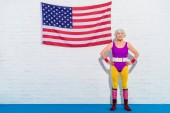 happy senior woman standing with hands on waist near us flag and smiling at camera
