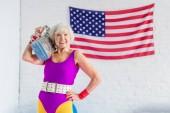 Fotografie glücklich senior Sportlerin holding Tonbandgerät und lächelt in die Kamera