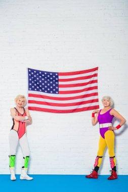 Full length view of beautiful senior sportswomen standing near american flag and smiling at camera stock vector