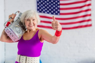 happy senior woman in sportswear holding tape recorder and showing thumb up
